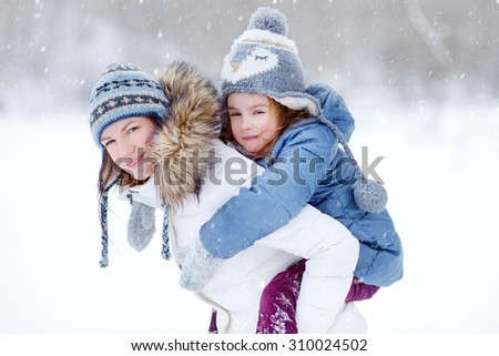 Young mother and her daughter having fun on winter day during snowfall - stock photo