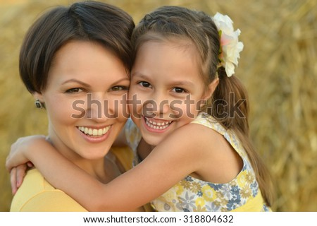 Young mother and her daughter on nature at summer - stock photo