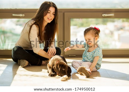 Young mother and her daughter playing and hanging out with their new puppy at home - stock photo