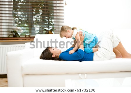 young mother and her daughter playing at home - stock photo