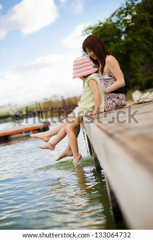 Young mother and her daughter splashing in the lake - stock photo