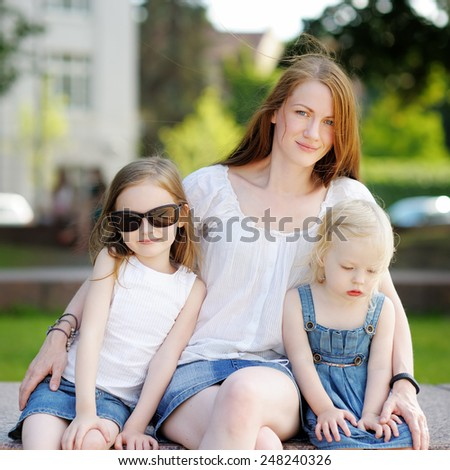 Young mother and her daughters outdoors at summer - stock photo