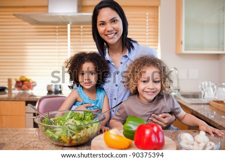 Young mother and her daughters preparing salad in the kitchen together - stock photo