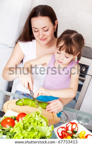 young mother and her five year old daughter cook together on the kitchen at home - stock photo