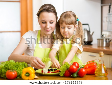 Young mother and her kid making vegetable salad - stock photo
