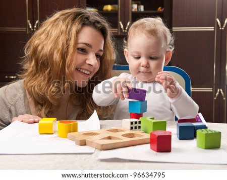 Young mother and her little baby daughter building tower with toy blocks - stock photo