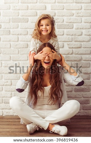 Young mother and her little daughter are looking at camera and smiling, sitting against white brick wall. Girl is closing her mother eyes - stock photo
