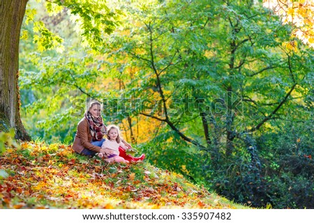 Young mother and her little daughter at beautiful autumn park. Kid girl and woman playing with yellow foliage. Family portrait outdoors. - stock photo
