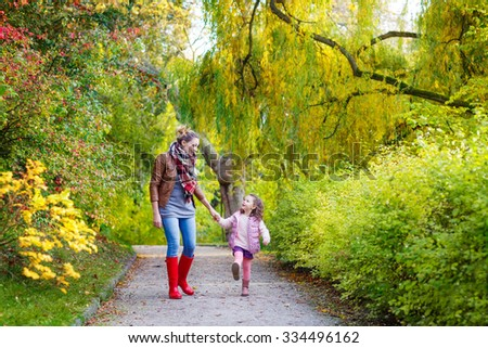 Young mother and her little daughter at beautiful autumn park. Kid girl and woman walking and having fun. Family portrait outdoors. - stock photo