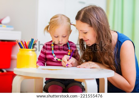 Young mother and her little daughter drawing together - stock photo