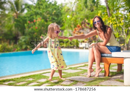 Young mother and her little daughter have fun near the swimming pool - stock photo