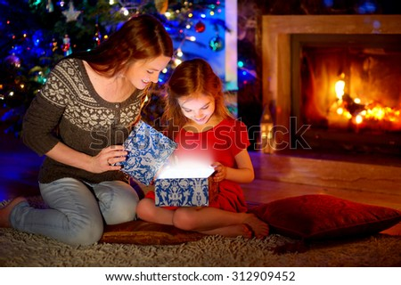 Young mother and her little daughter opening a magical Christmas gift by a Christmas tree in cozy living room in winter