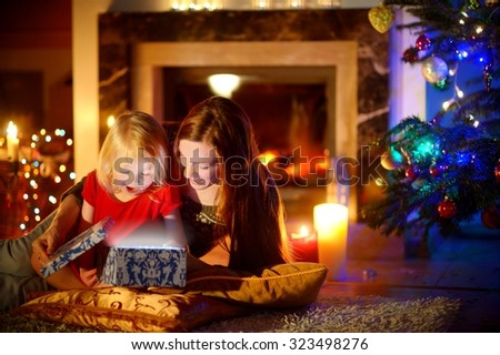 Young mother and her little daughter opening a magical Christmas gift by a Christmas tree in cozy living room in winter - stock photo