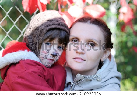 Young mother and her little daughter with face painting outdoors at fall day - stock photo