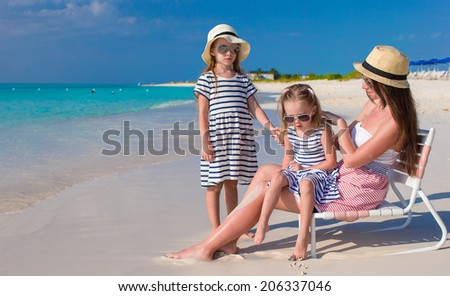 Young mother and her little daughters enjoy summer vacation