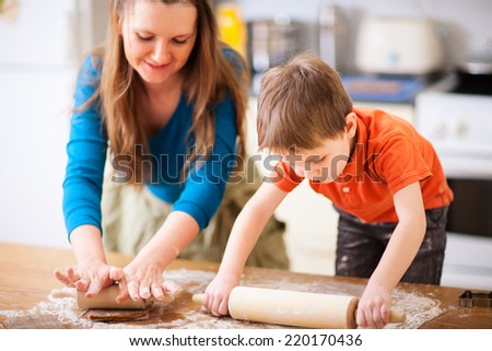 Young mother and her little son baking cookies together at home kitchen - stock photo