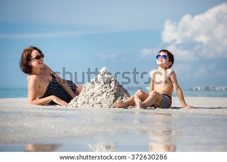 Young mother and her little son building sand castle at beach on Florida summer holiday vacation - stock photo
