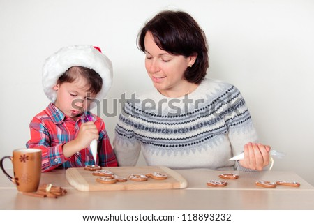 Young mother and her little son decorating the gingerbread cookies