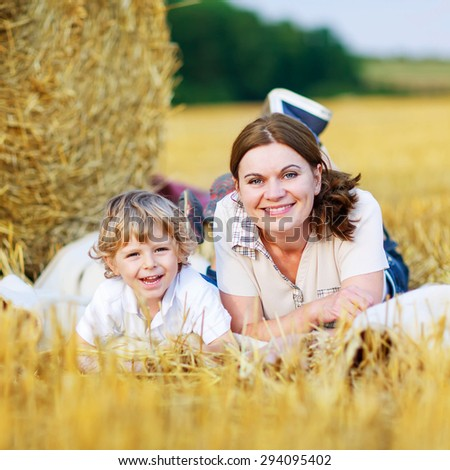 Young mother and her little son having fun at picnicking on yellow hay field in summer. Happy family of two enjoying nature and togetherness. - stock photo