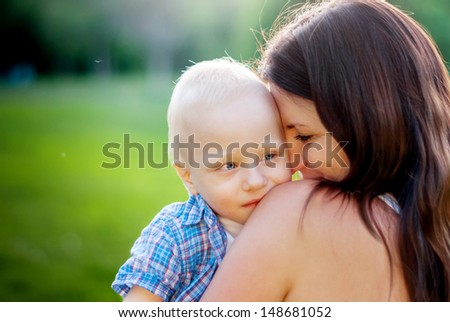 Young Mother and her little son on a nature background - stock photo
