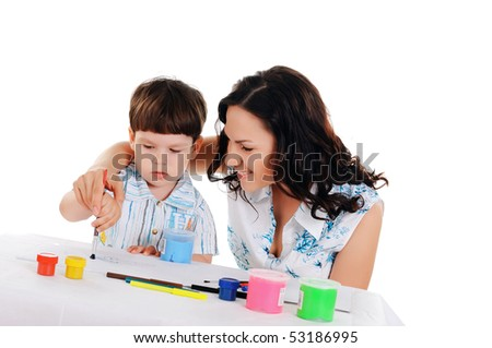 young mother and her little son paint colors in this album - stock photo
