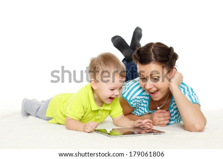 Young mother and her little son with computer tablet lie on a white background. Happy family. - stock photo