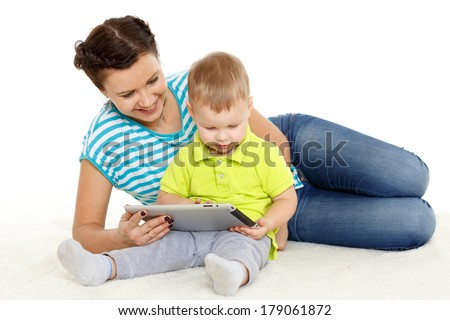 Young mother and her little son with computer tablet sit on a white background. Happy family. - stock photo