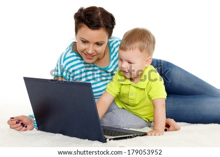 Young mother and her little son with notebook sit on a white background. Happy family.