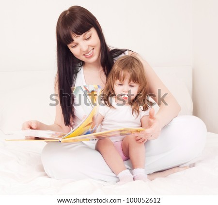 young mother and her one year old daughter reading a book in bed at home - stock photo