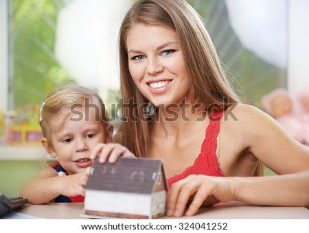 Young mother and her small daughter sitting with house miniature at the desk indoors. Concept of mortgage and apartment purchase.  - stock photo