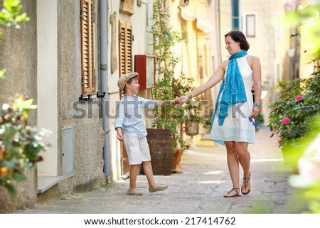 Young mother and her son playing outdoors in city - stock photo