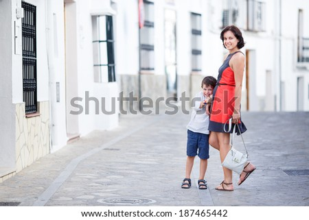 Young mother and her son playing outdoors in city on beautiful summer day - stock photo