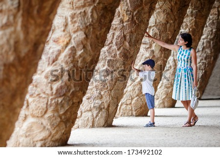 Young mother and her son walking Park Guell - stock photo