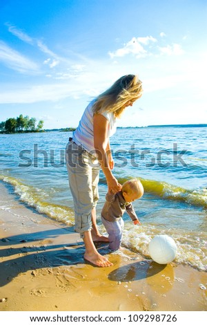 Young mother and her toddler walking on beach - stock photo