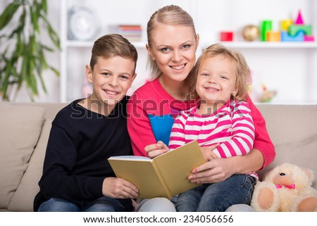 Young mother and her two children are reading a book together. Happy family. - stock photo