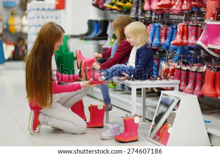 Young mother and her two little girls choosing and trying on new rain boots in a supermarket - stock photo