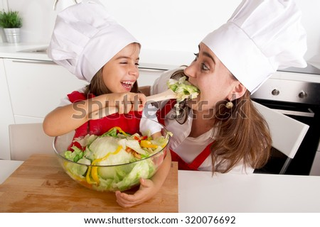 young mother and little daughter at home kitchen having fun and joking with salad bowl wearing apron and cook hat playing together in healthy vegetables nutrition education concept - stock photo