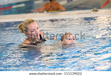 Young mother and little son in a swimming pool - stock photo