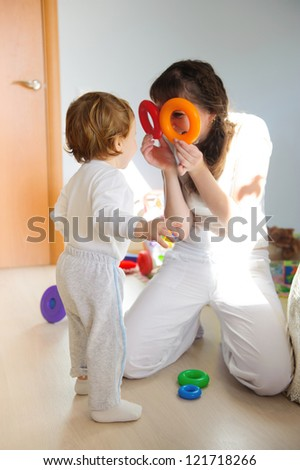 Young mother and little son playing at home