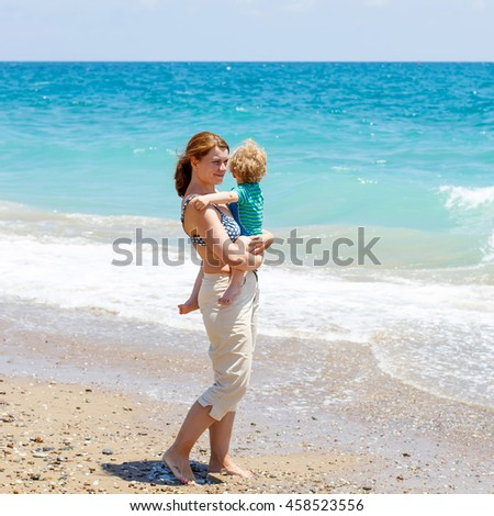 Young mother and little toddler boy having fun on beach of ocean. woman and kid son hugging. Carefree childhood and happy parenting. - stock photo