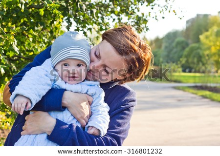 Young mother and newborn baby cute outdoor portrait - stock photo