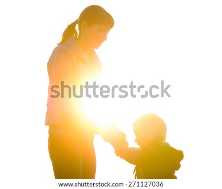 Young mother and son holding hands and laughing on the background of the backlight. family composition