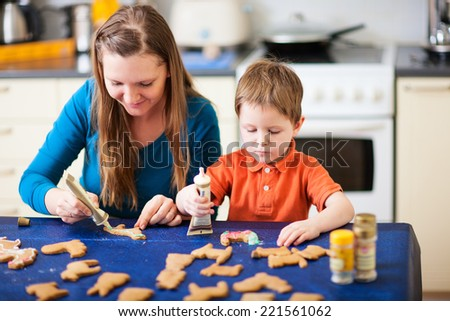 Young mother and son in home kitchen making cookies
