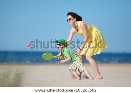 Young mother and son playing on the beach - stock photo