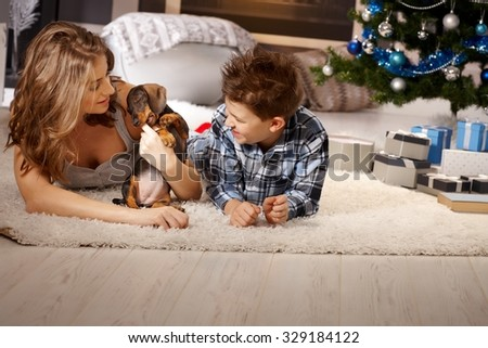 Young mother and son playing with puppy at christmas time, lying on floor. - stock photo