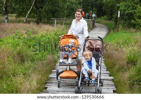Young mother and two little boys in summer nature park in Germany - stock photo
