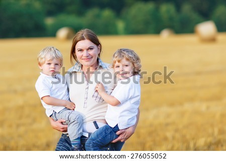 Young mother and two little twins kid boys having fun on yellow hay field in summer. Happy family of three enjoying nature and togetherness. - stock photo