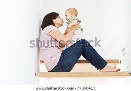 Young mother at home with her little baby on stairs. - stock photo
