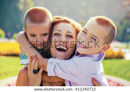 Young mother being embraced by her two little sons laugh infront of colorful summer flowers in a park.