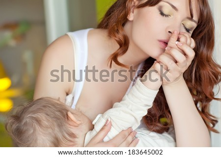 young mother breast feeding her infant - stock photo